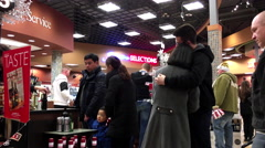 People line up for paying wine inside BC liquor store Stock Footage