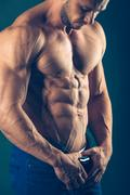 Strong athletic man  on black background. To pump the abdominals Stock Photos