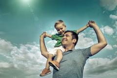 Stock Photo of Son seating on the father under beautiful sky