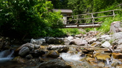 Time lapse - small river in the mountain with a small wood bridge Stock Footage