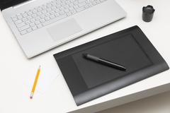 Digital drawing tablet and laptop on the table Stock Photos