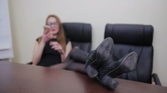 Woman talking on a phone with legs on a desk Stock Footage