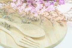 Wooden set of food utensil and static flower - stock photo