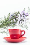 Stock Photo of Red cup of cofee and static flower