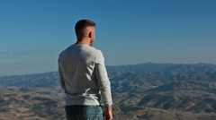 Young man celebrating success on top of a mountain Stock Footage