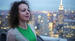 Woman smiles and stands on observation deck on roof of tall building Stock Footage