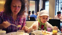 Happy mother and daughter eat fresh meal in restaurant Stock Footage