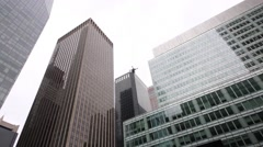 Man remote controls quadrocopter among glass skyscrapers Stock Footage