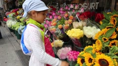 Girl looks at many flowers in street shop and touches sunflowers Stock Footage