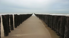 Breakwaters on a cloudy beach - North Sea in Domburg - Netherlands - stock footage