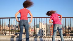 Mother and daughter do exercises on roof in New York at morning Stock Footage