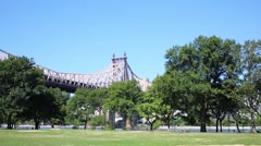 Queensboro bridge, East river and green trees in New York Stock Footage