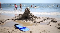 Sand castle, water of sea and resting people out of focus Stock Footage