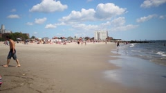 People rest near sea on Brighton Beach in NYC, United States Stock Footage