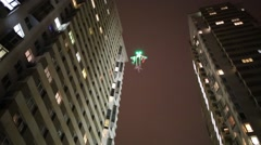 Flying illuminated helicopter ghost at night among buildings Stock Footage