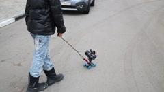 Legs of boy with camera on roller on asphalt near cars Stock Footage