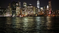 Skyscrapers near river in New York city and moving ship at night Stock Footage
