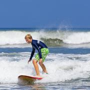 A boy 12 years surfing Kuta Legian beach and surfing paradise Bali Indonesia Stock Photos