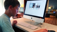 Boy (with MR) works with computer Apple in Boston, United States. Stock Footage