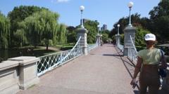 People walk on Mini Suspension Bridge in Boston Public garden Stock Footage