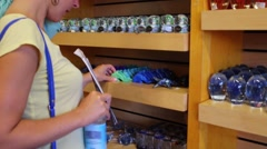 Woman choose maritime souvenirs in shop. Focus on shelves Stock Footage