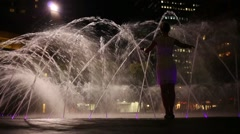 Woman touches water of fountain with illumination and goes away Stock Footage