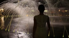 Woman in dress goes into fountain with illumination at night Stock Footage