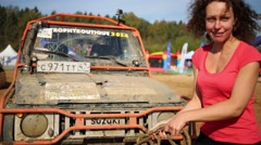 Woman holds rope of car in off-road competition Stock Footage