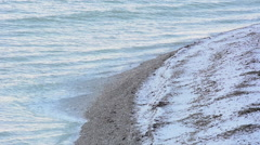 Waves hitting a limestone pebble beach on the island of Gotland in Sweden Stock Footage