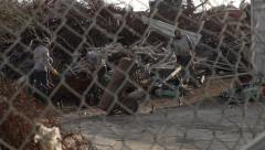 Men Working on a Scrap Yard. Wiring in the foreground. - stock footage