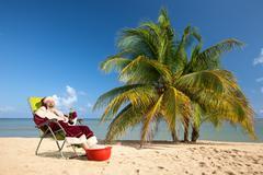Santa Claus sitting in deck chair on beach Stock Photos