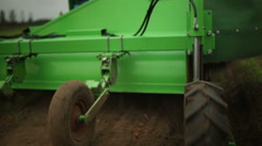 Trailer attached to a tractor going over a field, tight shot of wheels Stock Footage