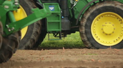 Close shot of large tractor wheels harvesting a field Stock Footage