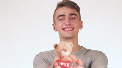 Handsome Guy Gives a Gift to His Girlfriend. In the hands of a guy toy teddy - stock footage
