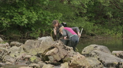 Female researchers electro fishing in a river to count Eels Stock Footage
