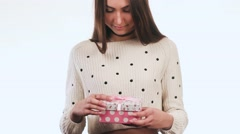 Very beautiful girl opens a gift. She is very happy. She smiles and laughs. Stock Footage
