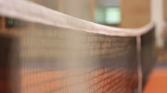 Man erecting a tennis net in an indoor tennis court Stock Footage