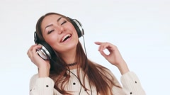 Beautiful girl listens to music in headphones and dancing. The girl smiles. She Stock Footage
