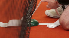 Man erecting a tennis net in an indoor tennis court Stock Footage