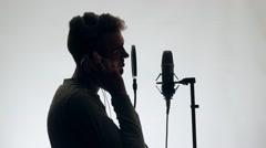 Handsome Guy Sings in a Microphone Standing studio headphones. The guy standing Stock Footage