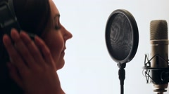Pretty Girl Singing Into Studio Microphone. The girl is wearing headphones on a Stock Footage