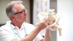 Mature doctor demonstrating lumbal spine with disci Stock Footage