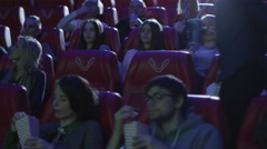 Couple is taking their seats while people are watching a film in a cinema Stock Footage