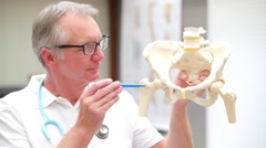 Mature doctor demonstrating hip joint Stock Footage
