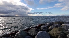 Seattle Sound rocky coast and peir Slow pan Camera left Stock Footage