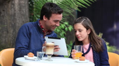 Man with a girl in a coffee using the ipad - stock footage