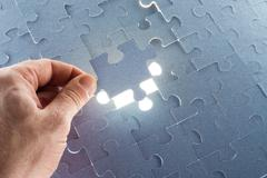 Stock Photo of Missing jigsaw puzzle piece with light glow
