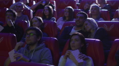 Couple is making out and kissing while watching a film screening in a cinema - stock footage