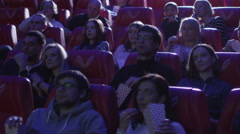 Man exit from his seat while people are watching a film screening in a cinema - stock footage