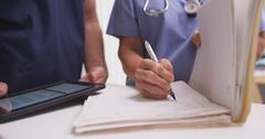 Close-up of mature female nurse writing in a patient's folder Stock Photos
